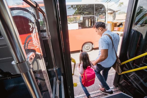 Asiatischer vater bringt seine tochter mit öffentlichen verkehrsmitteln zur schule