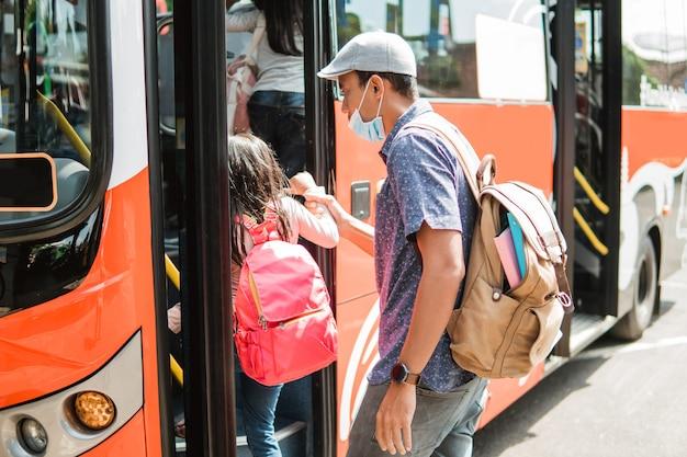 Asiatischer vater bringt seine tochter zur schule, indem er mit öffentlichen verkehrsmitteln mit dem bus fährt und eine gesichtsmaske trägt