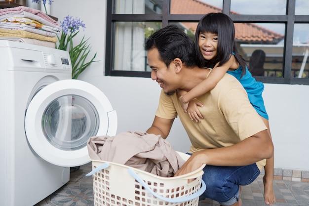 Asiatischer vater, der huckepack spielt, reitet zusammen mit tochter, während wäsche mit waschmaschine macht