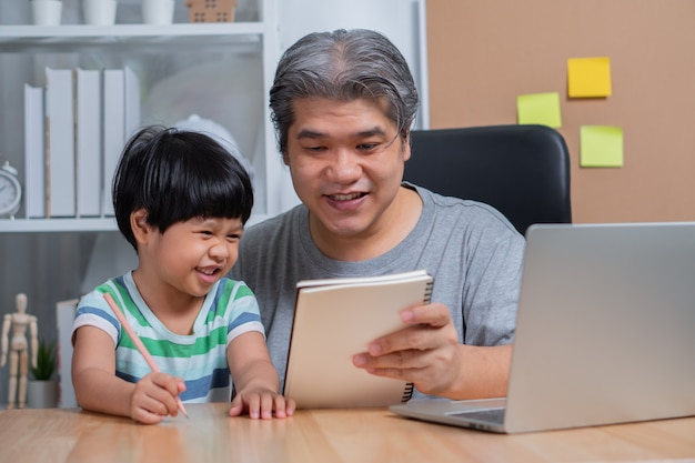 Asiatischer vater, der mit einem laptop im heimbüro arbeitet und hausaufgaben mit einer tochter unterrichtet.