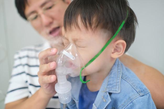 Asiatischer vater, der seinem kleinkindsohn bei der inhalationstherapie durch die maske des inhalators hilft. krankes kleines kind mit atemproblemen mit sauerstoffmaske atmet durch vernebler