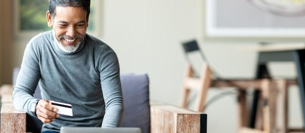 Asiatischer vater des attraktiven bärtigen hippies oder hispanischer alter mann, der laptop verwendet