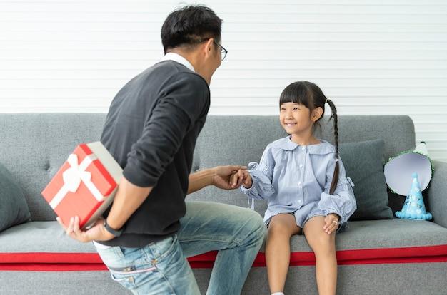 Asiatischer vater gibt geschenk für tochter. konzept überraschungsgeschenkbox zum geburtstag.