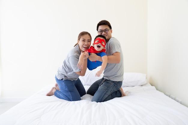 Asiatischer vater, mutter und sohn spielen superhelden auf dem bett im schlafzimmer. freundliche familie, die spaß hat