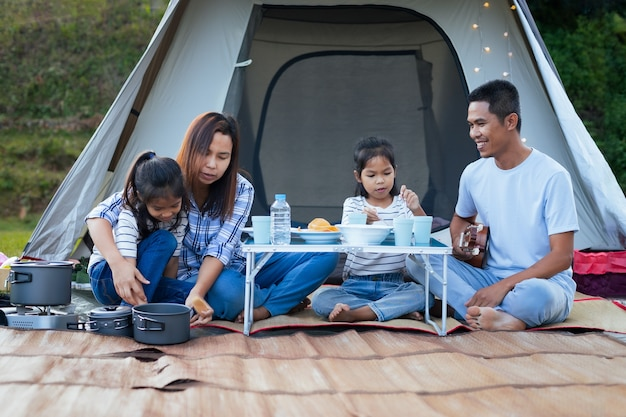 Asiatischer vater, mutter und zwei kindermädchen, die spaß haben, außerhalb des zeltes auf dem campingplatz in der schönen natur zu picknicken.
