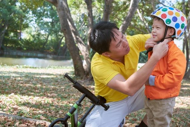 Asiatischer vater setzte sturzhelm auf nettes kleines 3 jahre alte kleinkindjungenkind, -vati und -sohn, die spaß mit balancenfahrrad (lauffahrrad) auf natur am park haben