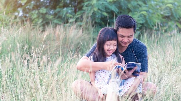 Asiatischer vater sitzt auf gras mit kleiner tochter, die auf ihm sitzt und ein buch liest. 16: 9 stil