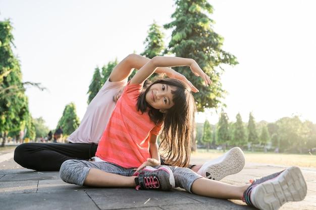 Asiatischer vater und kleine tochter machen übungen im freien. gesunder lebensstil der familie mit kind