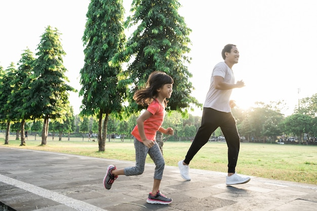 Asiatischer vater und kleine tochter machen übungen im gesunden lebensstil der familie mit kind im freien