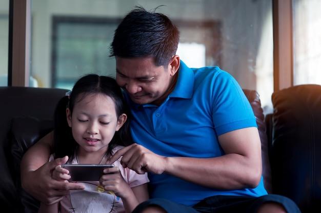 Asiatischer vater und seine tochter, die zu hause smartphone verwendet