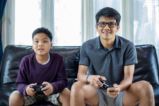Asiatischer vater und sohn spielen gerne videospiele zusammen mit einem video-joystick mit spannung und viel spaß im wohnzimmer zu hause