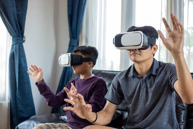 Asiatischer vater und sohn spielen gerne videospiele zusammen mit video-joystick und virtual reality-brille mit aufregendem und sehr viel spaß im wohnzimmer zu hause