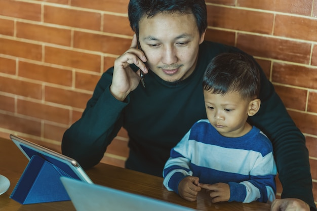 Asiatischer vati mit sohn schauen die karikatur über technologielaptop zusammen mit dem telefonbenennen