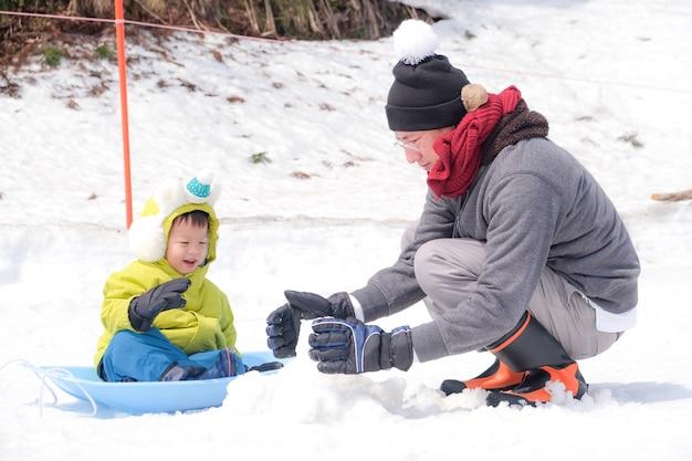 Asiatischer vati und sohn, die glücklich im schnee während der winterurlaubferien spielt