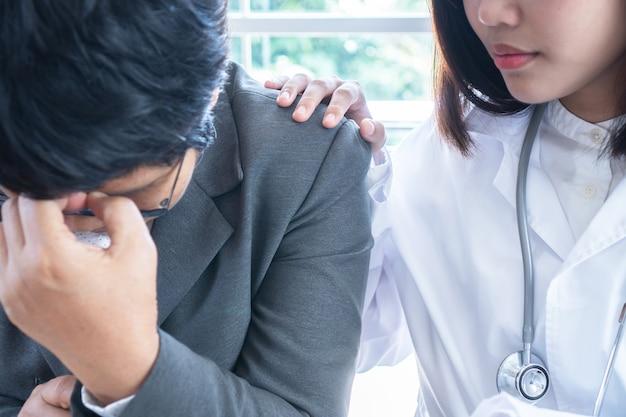 Asiatischer weiblicher doktornotenschulterpatienten von mittlerem alter mit freundlicher ermutigung