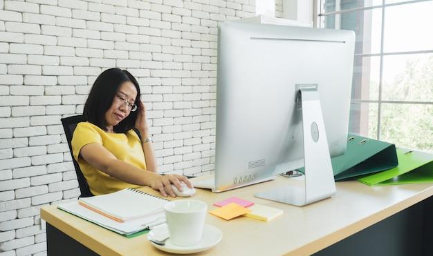 Asiatischer weiblicher firmenangestellter oder geschäftsmann, der am schreibtisch im büro sitzt
