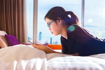 Asiatischer weiblicher Jugendlicher, der ihr intelligentes Telefon im Bett, Morgensonnenlicht mit Aufflackern verwendet