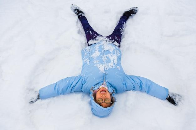 Asiatischer weiblicher jugendlicher, der sich genießt, schneeengel machend