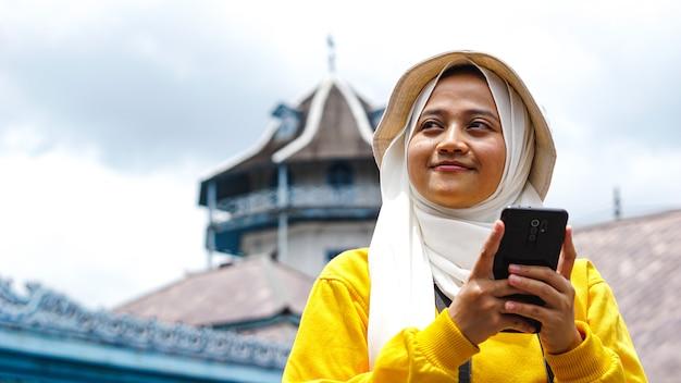 Asiatischer weiblicher reisender mit einer kamera, die das telefon hält