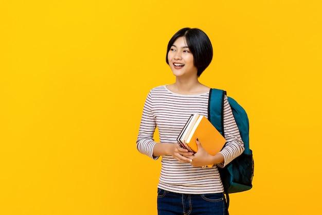 Asiatischer weiblicher student mit dem rucksack, der bücher hält
