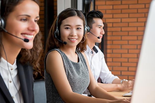 Asiatischer weiblicher telemarketing-kundendienstmitarbeiter, der in call-center arbeitet