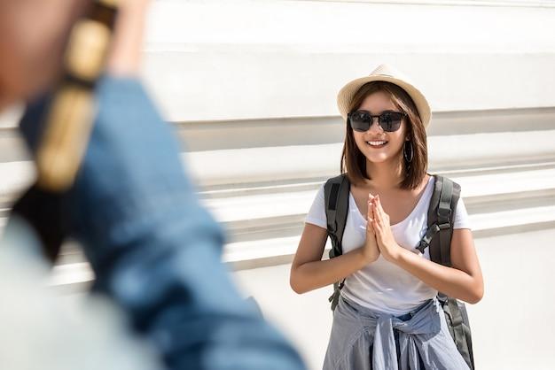 Asiatischer weiblicher touristischer wanderer, der wai, thailändischer gruß, beim reisen in bangkok thailand fungiert