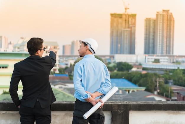 Asiatischer wirtschaftsingenieur, der mit blaupause arbeitet.
