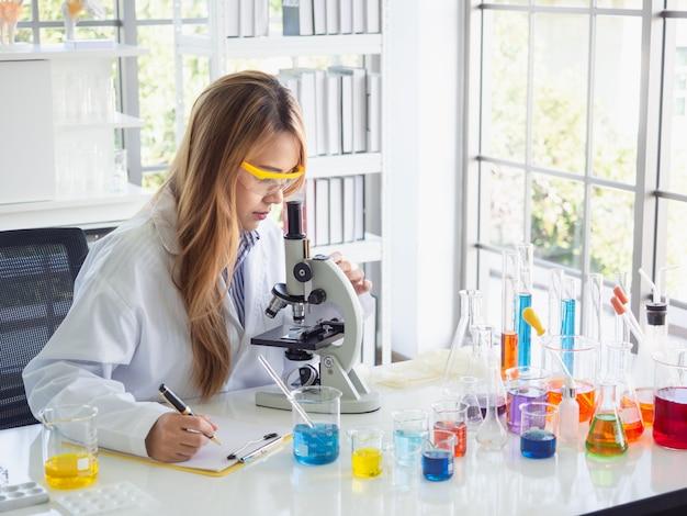 Asiatischer wissenschaftler, der im labor mit mikroskop arbeitet