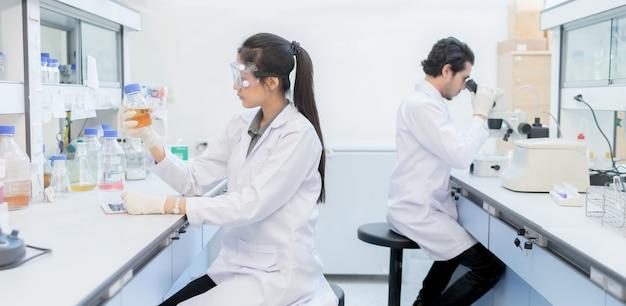 Asiatischer wissenschaftler im labor, das am labor mit reagenzgläsern arbeitet