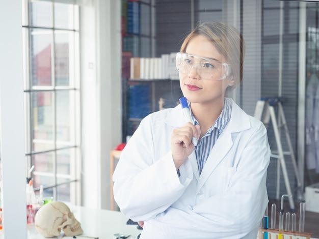 Asiatischer wissenschaftler schreibt eine formel auf eine glasplatte und denkt etwas
