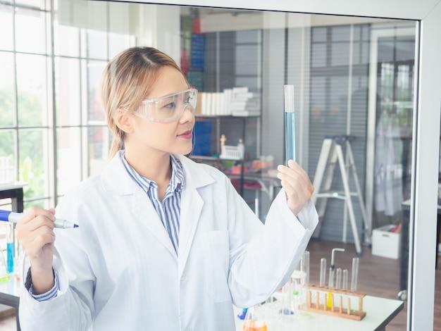 Asiatischer wissenschaftler schreibt eine formel auf eine glasplatte