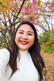 Asiatischer woment mit dem langen schwarzen haar nimmt das lächelnde selfie, porträt mit blumen