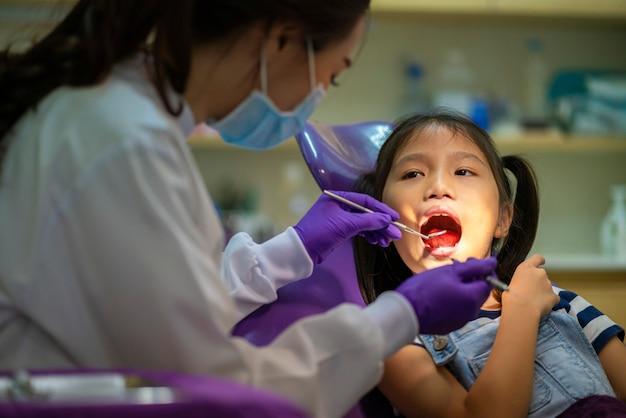 Asiatischer zahnarzt überprüft kleine asiatische mädchenzähne gesund in der zahnarztpraxis.