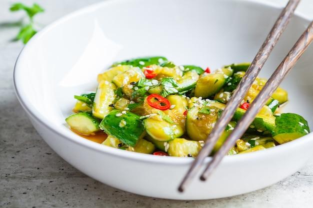 Asiatischer zertrümmerter gurkensalat mit paprika- und sesamsamen in der weißen schüssel. chinesisches essen-konzept.