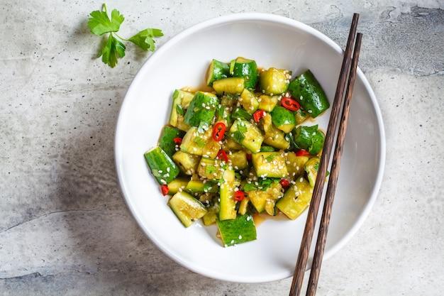 Asiatischer zertrümmerter gurkensalat mit paprika- und sesamsamen in der weißen schüssel, draufsicht. chinesisches essen-konzept.