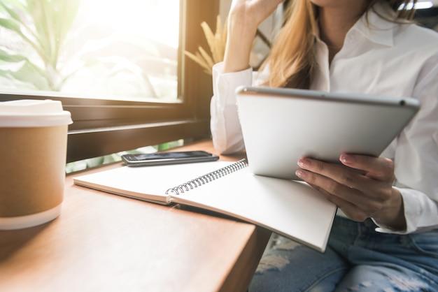 Asiatischer zufälliger frauenfreiberufler, der tablette verwendet und plan und lächeln mit kaffeetasse im caférestaurant schreibt