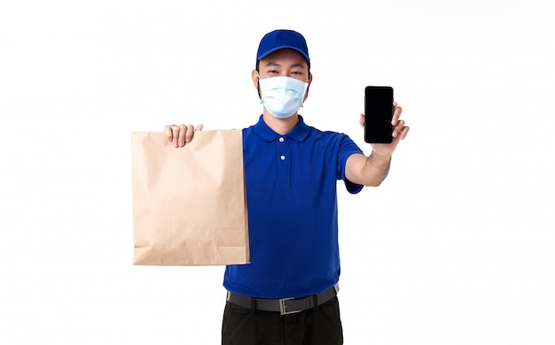 Asiatischer zusteller, der gesichtsmaske in blauer uniform mit smartphone hält, die papiertüte lokalisiert auf weißem hintergrund hält. express-lieferservice während covid19.