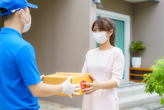 Asiatischer zusteller, der gesichtsmaske trägt, die einen karton hält