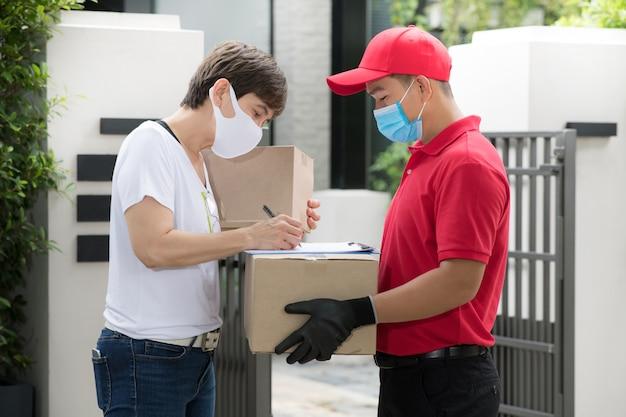 Asiatischer zusteller, der gesichtsmaske und handschuhe in der roten uniform trägt, die paketbox zum empfänger liefert
