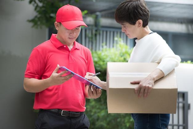 Asiatischer zusteller in roter uniform, die paketbox an empfängerin zu hause mit empfängerzeichen liefert, um das paket auf klemmbrett zu erhalten