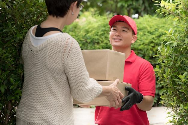 Asiatischer zusteller in roter uniform, die paketbox zum weiblichen empfänger zu hause liefert
