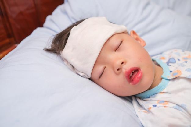 Asiatisches 3 - 4 jahre altes kleinkind bekommt hohes fieber, wenn es mit einer kalten kompresse, einem feuchten waschlappen auf der stirn im bett liegt, um schmerzen zu lindern, fieber abzukühlen,