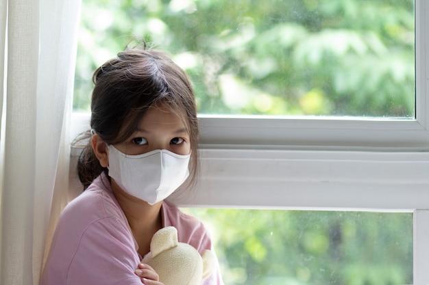 Asiatisches 6 oder 7 jahre altes kind mit medizinischer maske. kleines mädchen, das am fenster steht und nach draußen schaut. sie sieht traurig und gelangweilt aus. sie kann krank sein oder unter quarantäne der coronavirus-krankheit 19 (covid-19).