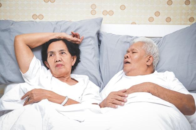 Asiatisches älteres ehepaar schlafen im bett im schlafzimmer