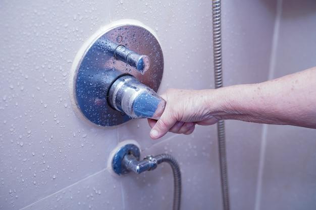 Asiatisches älteres oder älteres geduldiges gebrauchstoilettenbadezimmer der alten dame, zum der dusche in der krankenpflegestation zu öffnen