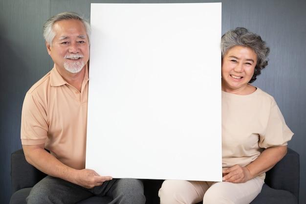 Asiatisches älteres paar, das auf sofa sitzt und weißes leeres plakat zusammenhält.