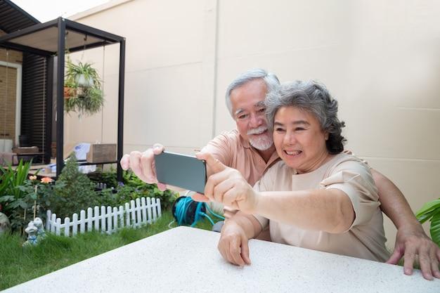 Asiatisches älteres paar, das ein selbstfoto zusammen mit smartphone zu hause macht.