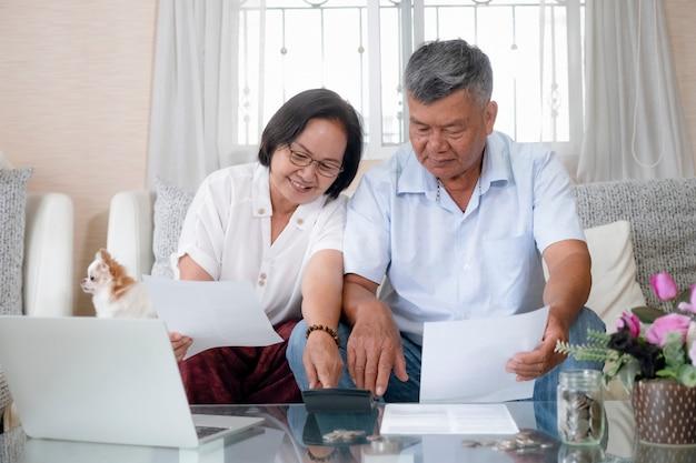 Asiatisches älteres paar, das hausfinanzen tut und berechnet.
