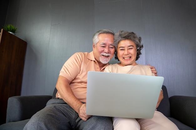 Asiatisches älteres paar, das im videoanruf-chat auf laptop-computer spricht, intelligente technologie für alter und online-aktivismus, das verbundenes konzept bleibt