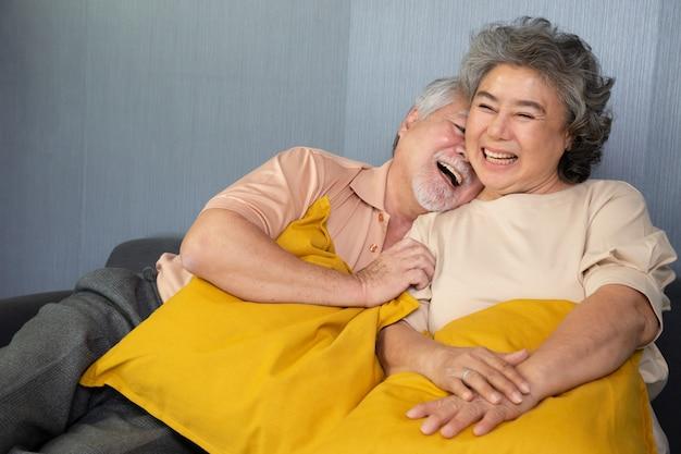 Asiatisches älteres paar, das lachend auf sofa zu hause sitzt.